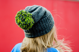 View of a blonde woman's back of head wearing a blue slouch hat with ribbed brim folded up and a bright green pom pom.