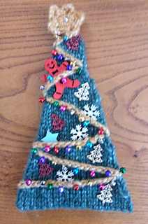 Tree decorated with mustard yellow crochet chain with tiny bell ornaments, wooden trees card toppers and a wood gingerbread man