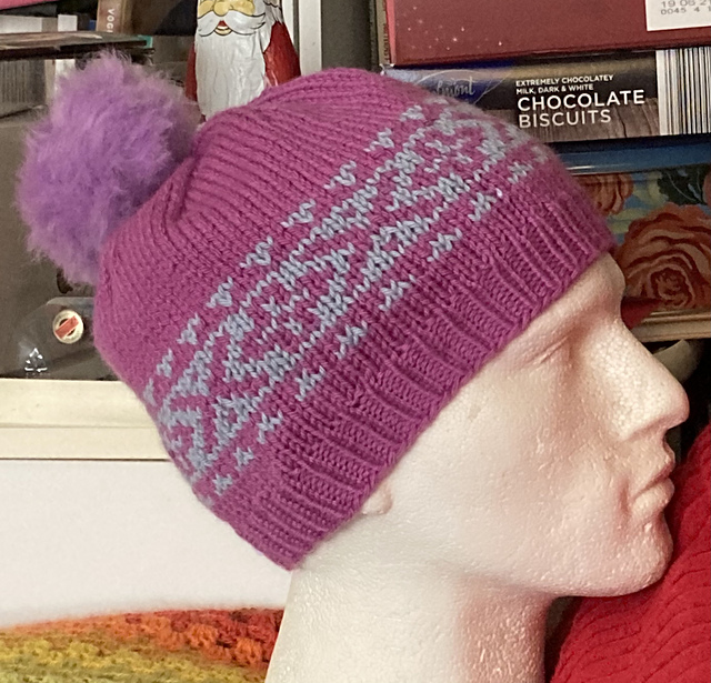 The Big Crush Hat by Faye Kennington, shown in Japonica Pink for the main colour and light blue for the contrast with a pink faux fur pompom.