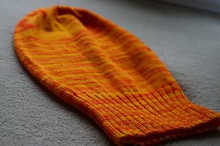 View of a semi-solid orange knit Sockhead hat lying flat.