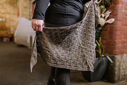 Lena is holding Acorn, a top-down triangular shawl, filled with an easy-to-memorize geometric lace pattern.