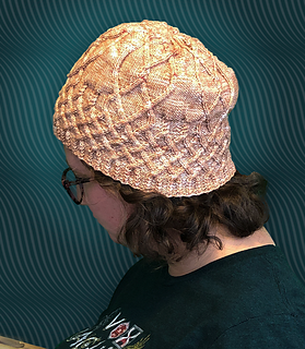 Ribbing, lattice cables, and hourglass and fire shaped cables come together to create a hat!