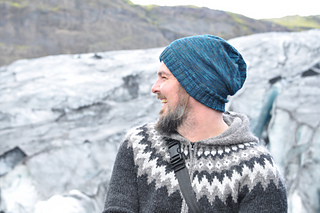 Man with beard laughing and wearing a blue slouchy knit hat and a fairisle sweater in grey tones standing in front of rocks.