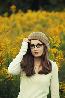 Brunette woman with long hair and beige long-sleeved shirt wearing glasses and a fawn-coloured slouchy knit hat with the ribbed brim folded up and goldenrod in the background.