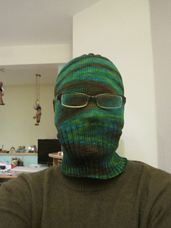 Person wearing a green Sockhead hat pulled down completely over face with glasses worn overtop.