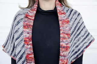 This styling shows the poncho doubled over and worn as a shawl.
