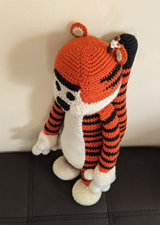 Large crochet tiger plushie standing with hands down their sides. A lego figure stands on the head to show scale of the plushie.