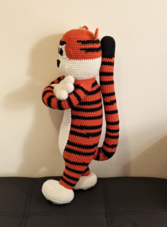 Large crochet tiger plushie standing with arms crossed looking to the left.