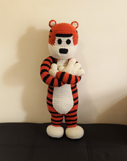 Large crochet tiger plushie standing facing the camera with arms crossed looking sassy.