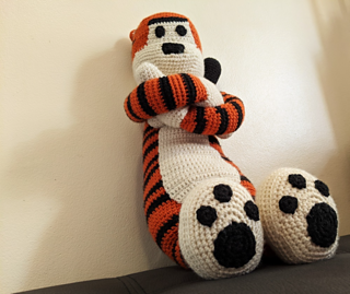 Large crochet tiger plushie sitting with arms crossed, the photo perspective is from below so the size is emphasised.