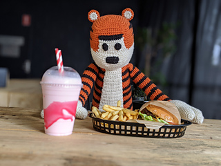 Large crochet tiger plushie sitting at a wooden table with a milkshake, burger and fries in front.