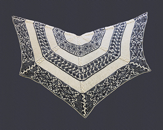 Cables reminiscent of braided leather and knitted mosaics of flowers and lightning combine to form one large, wing-shaped shawl.
